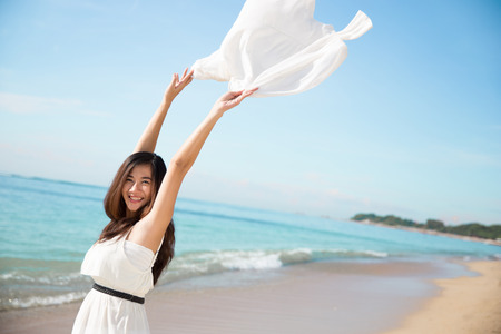 Excited portrait of a asian woman enjoying the beach Stock Photo
