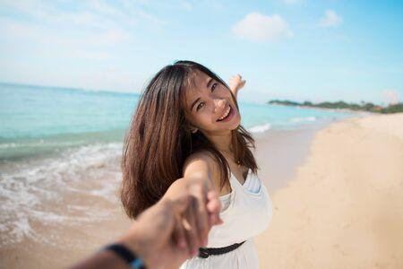 family happy: Retrato de una mujer joven feliz que se ejecuta en la playa mientras tira su brazo novios Foto de archivo
