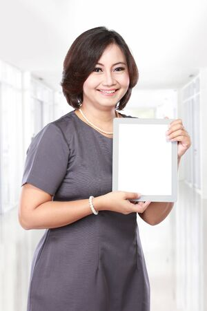 blank tablet: elegant middle aged businesswoman showing blank tablet