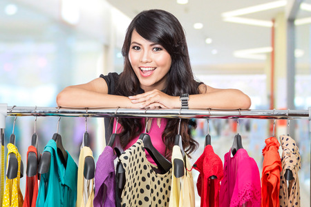 A portrait of a beautiful woman posing on the rack of clothes in a shop