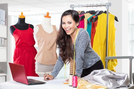 Een portret van een jonge Aziatische ontwerper vrouw met behulp van een laptop en glimlachend, kleding opgehangen als achtergrond Stockfoto