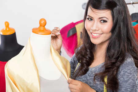 selfemployed: A portrait of a young asian designer sewing a fabric on a mannequin, smiling to the camera
