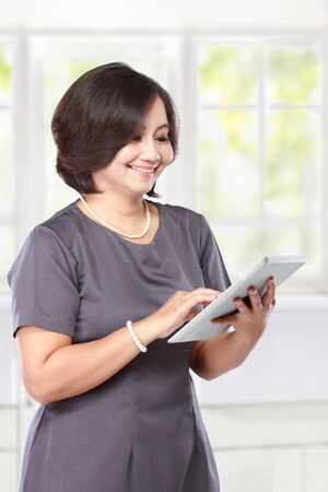 middle age women: elegant middle aged businesswoman with tablet computer