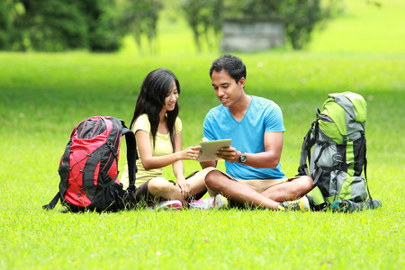 knapsacks: A portrait of a young asian couple sitting on the park looking a tablet pc