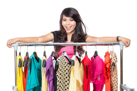 woman clothes: A portrait of a beautiful woman posing on the rack of clothes in a shop