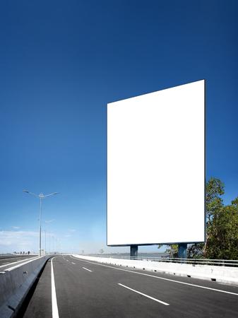 vertical: Tarjeta en blanco blanca en blanco o cartel o letrero en la carretera bajo el cielo azul brillante