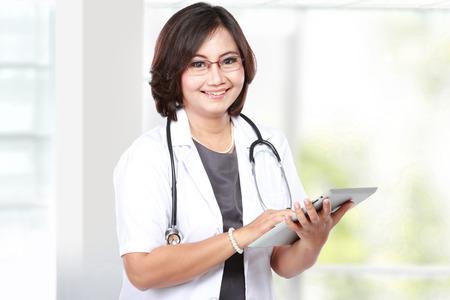 흰색 배경 위에 격리 태블릿 컴퓨터를 사용 하여 중간 세 여자 의사 스톡 콘텐츠