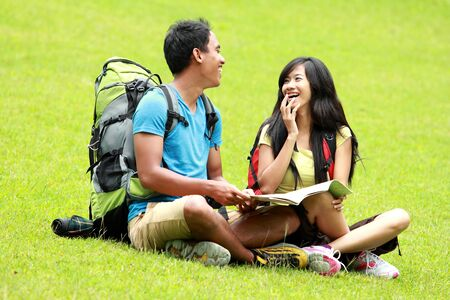 knapsacks: A portrait of a young asian couple chatting and sitting on the grass, map on the mans lap