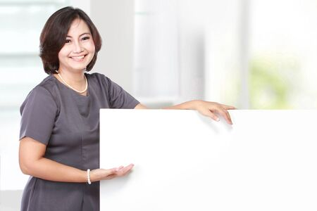 holds: smiling business woman showing blank signboard, isolated on white background
