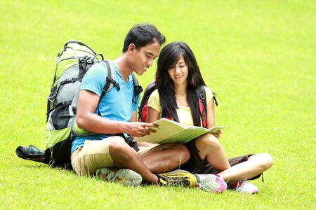 knapsacks: A portrait of a young asian couple read a map and sitting on the grass