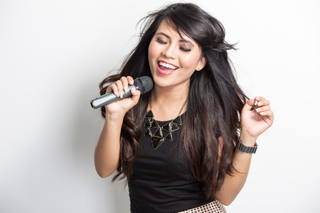 portrait of pretty young asian woman singing karaoke with a mike