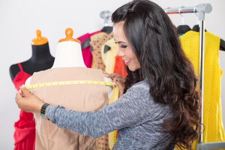 selfemployed: A portrait of a young fashion designer or Tailor working on a design or draft, she takes measure on a dressmakers dummy