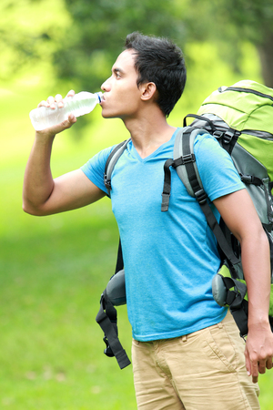 knapsacks: A portrait of a young asian man drinking water while travel backpacking, outdoor