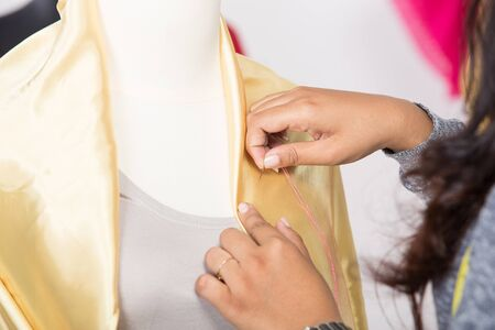 pinning: A portrait of a young asian designer pinning a fabrice on a mannequin, close up Stock Photo
