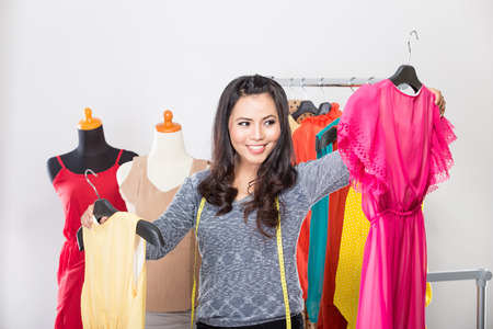 comparing: A portrait of a young asian designer comparing two dresses in her hands, smiling