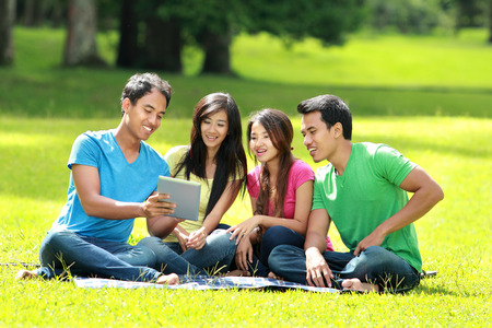 4 people: Portrait of Group of students studying in the park using tablet PC Stock Photo