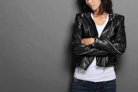 A portrait of asian young woman in black leather jacket on gray background