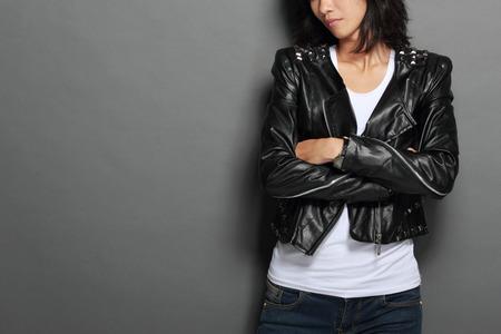 Een portret van Aziatische jonge vrouw in het zwart lederen jas op een grijze achtergrond Stockfoto