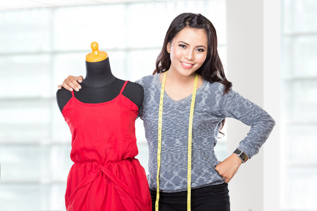 manequin: A portrait of a young asian designer woman with manequin or dummy posing smiling, hold a scissors,  look at the camera Stock Photo