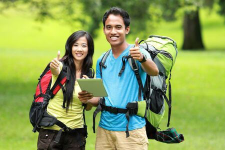 knapsacks: A portrait of a young asian couple on the park, holding a tablet pc showing thumbs up