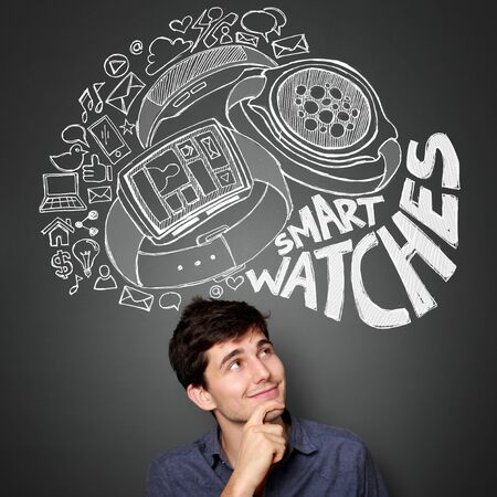 man looking up: young man looking up to the illustration of the concept of modern smart watch Stock Photo