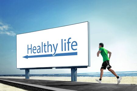 healthy sport: A portrait of a Asian young man running on beach, Sport healthy life concept with a big billboard