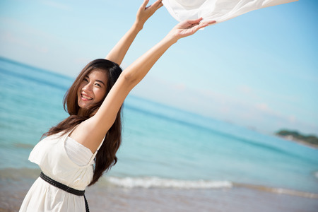 A portrait of an Asian woman enjoying her time in the beach, closing her eyes and arms open wide