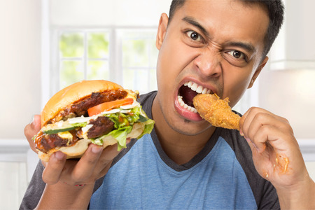 personas comiendo: Un retrato de un hombre joven muerde su palillo deliciosamente