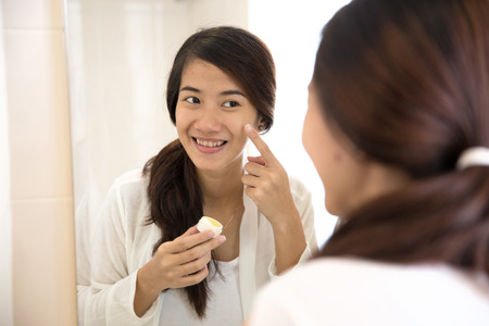 girl shirt: A portrait of a Happy asian woman putting make-up on, smiling at mirror Stock Photo