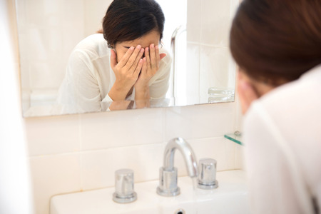cleanse: A portrait of an Asian woman washing her face on the sink