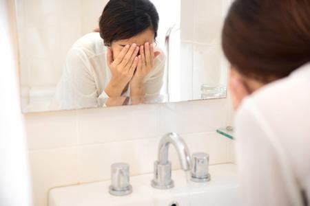 Een portret van een Aziatische vrouw die haar gezicht wast op de wastafel