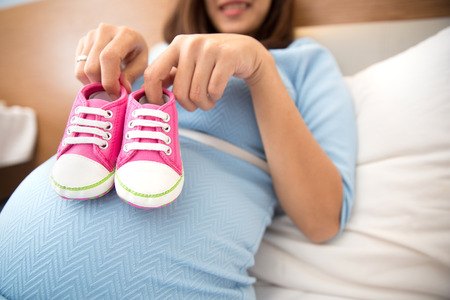motherly: A portrait of a Pregnant woman with a pair of pink sneakers baby shoes