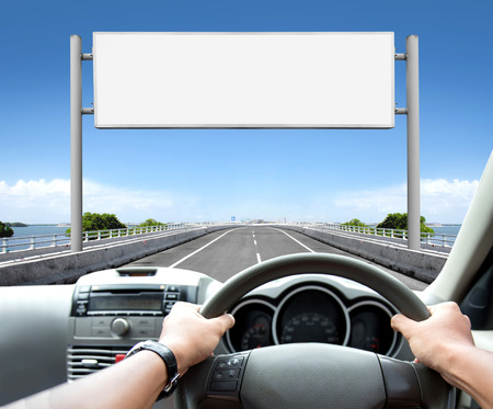 Man driving a car while looking at billboard or road sign ahead