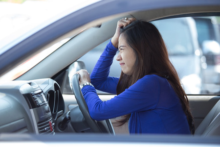 female driver: A portrait of a young asian woman on a ride, a car, frustrated Stock Photo
