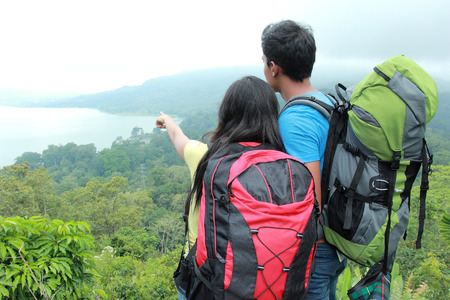 A portrait of a young asian couple travel backpacking, outdoor