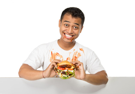 adult sandwich: A portrait of young man have a great desire to eat a burger standing with blank white board Stock Photo