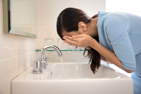 visage: Un portrait d'une femme asiatique laver son visage sur l'évier Banque d'images