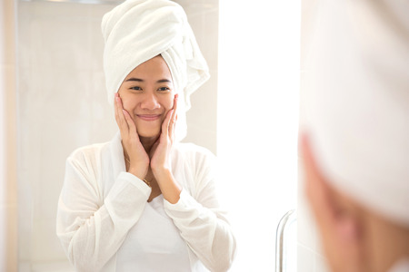 A portrait of a Young asian woman smile while looks at the mirror, happy Stock Photo