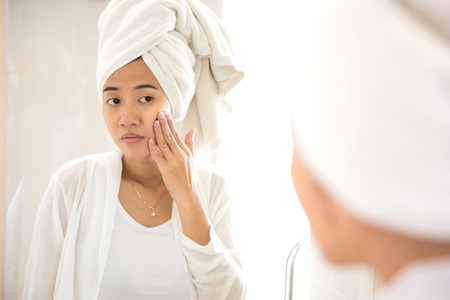 A portrait of an Young Asian woman taking care of her face