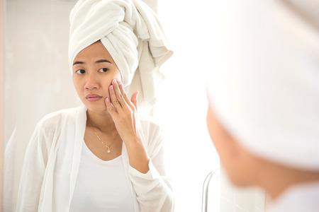 pulizia viso: Un ritratto di una giovane donna asiatica prendersi cura del suo viso