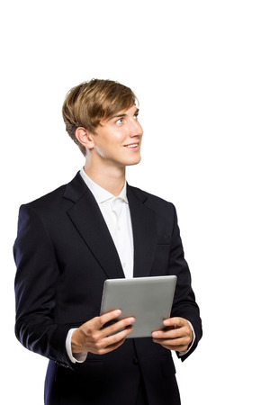 serious businessman: A portrait of a Young businessman in suit with a tablet pc on his hand, looking up