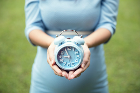 close up of woman hands holding an blue alarm clock, grass background