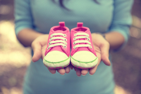 motherly: A portrait of a pregnant woman holding a pair of  pink sneakers baby shoes Stock Photo