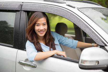 car inside: A portrait of a happy young asian woman riding a car Stock Photo
