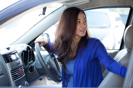 A portrait of a young asian woman on a ride a car. trying to reverse
