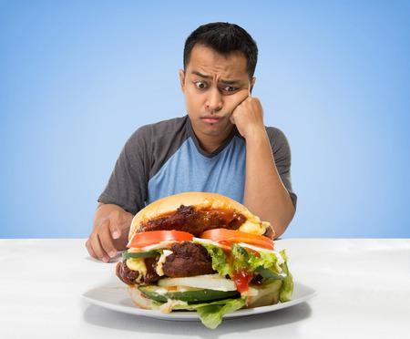 Een portret van een hongerige mens die grote hamburger voor hem Stockfoto