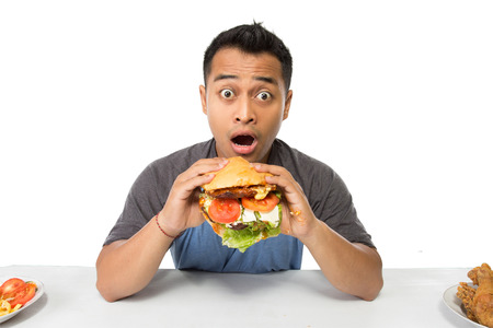 A portrait of young man have a great desire to eat a burger Stock Photo