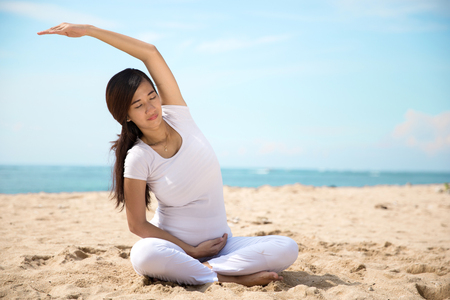 pregnant exercise: A portrait of a pregnant asian woman doing yoga in the sea shore