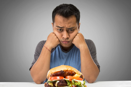 A portrait of a hungry man looking at big hamburger Stock Photo