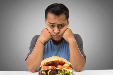 Een portret van een hongerige man te kijken naar grote hamburger Stockfoto